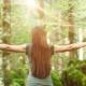 kvinde står meditativt med udstrakte arme i en skov