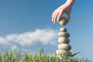 en rund kugle forsøges placeret ovenpå en stabel af 6 balancerende sten