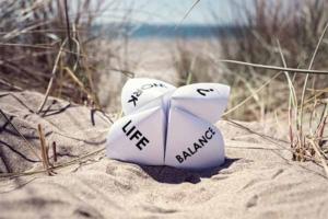 en nip-napper med ordene LIFE og BALANCE ligger i sandet