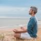 mand sidder i meditationsstilling ved stranden og har lukkede øjne