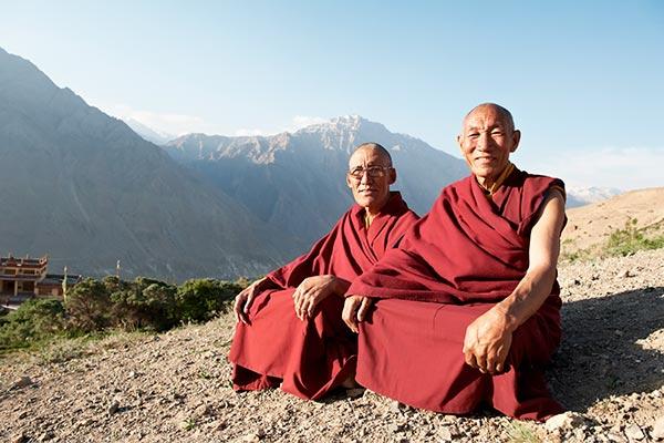 2 munke klædt i rødt sidder på bjergtop