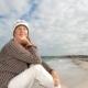 ældre kvinde sidder eftertænksomt i strandkanten