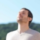 mand med lukkede øjne retter ansigtet op mod den blå himmel