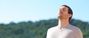 mand med hovedet vendt opad mod blå himmel